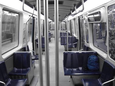 Intérieur d'un wagon du métro de Montréal avec les sièges bleu et le reste en noir et blanc