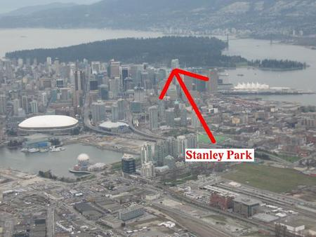 Vue aérienne de Vancouver. On y distingue la ville en gris au premier plan et le Stanley Park en vert foncé à l'arrière.